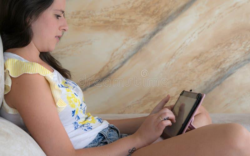 Jonge vrouw die een tabletcomputer met behulp van royalty-vrije stock afbeelding