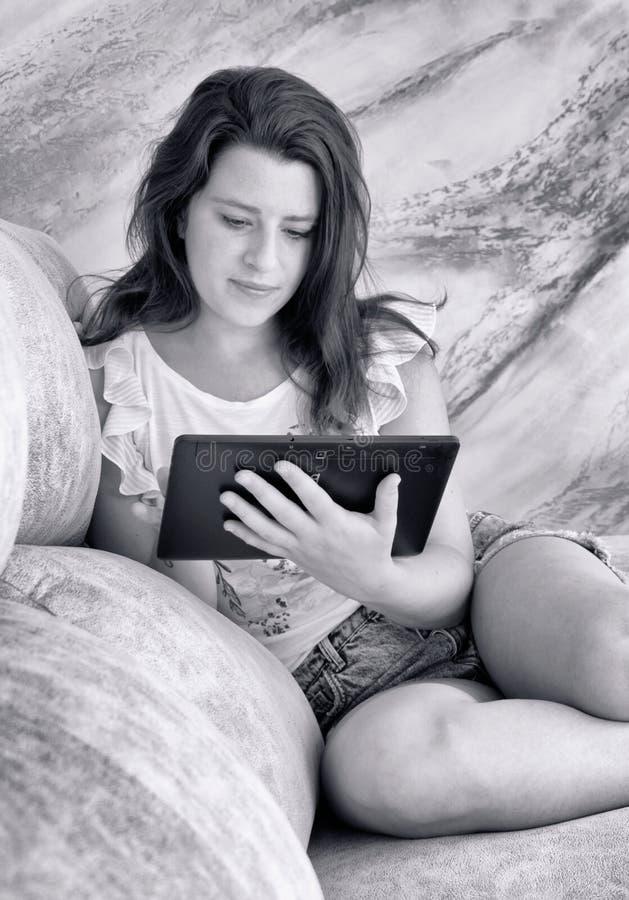 Jonge vrouw die een tabletcomputer met behulp van Rebecca 36 stock fotografie