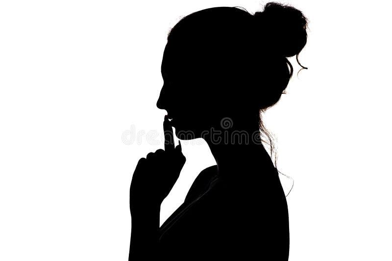 Jonge vrouw die een teken maken door vinger dichtbij lippen die stilte of geheim, silhouetprofiel van onbekend meisje met een bro stock foto