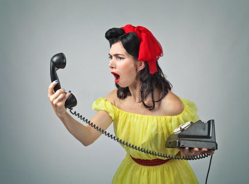 Jonge vrouw die in een telefoon gillen stock afbeelding