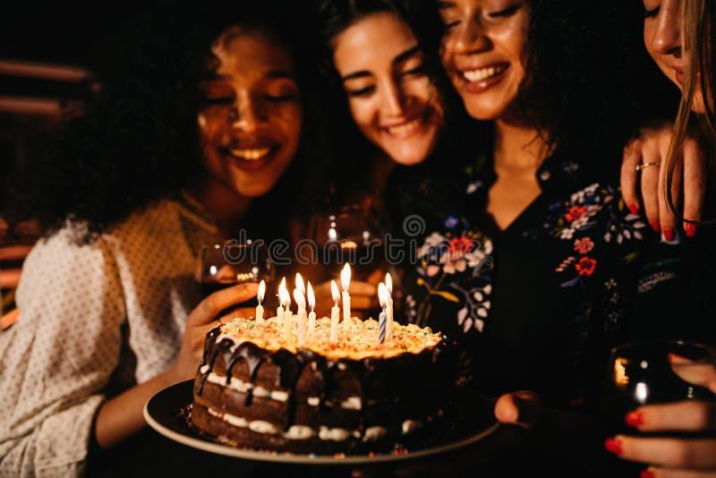 Jonge vrouw die een verjaardagscake houden stock afbeeldingen