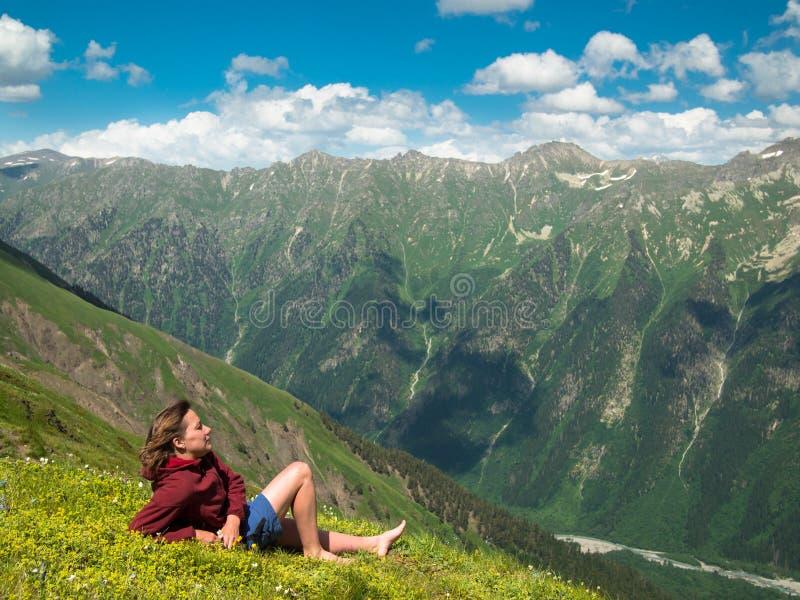 Jonge vrouw die in een weide met bloemen voor de bergketen Noord- van de Kaukasus liggen stock afbeelding