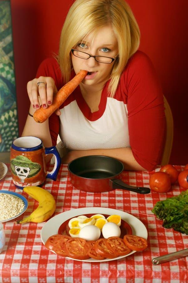 Jonge vrouw die een wortel eet stock foto's