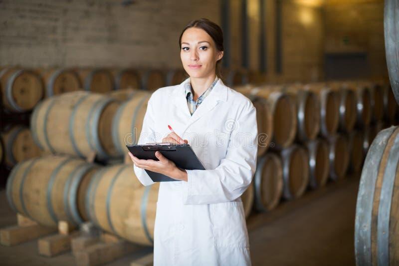 Jonge vrouw die eenvormige status in grote wijnkelder dragen stock fotografie