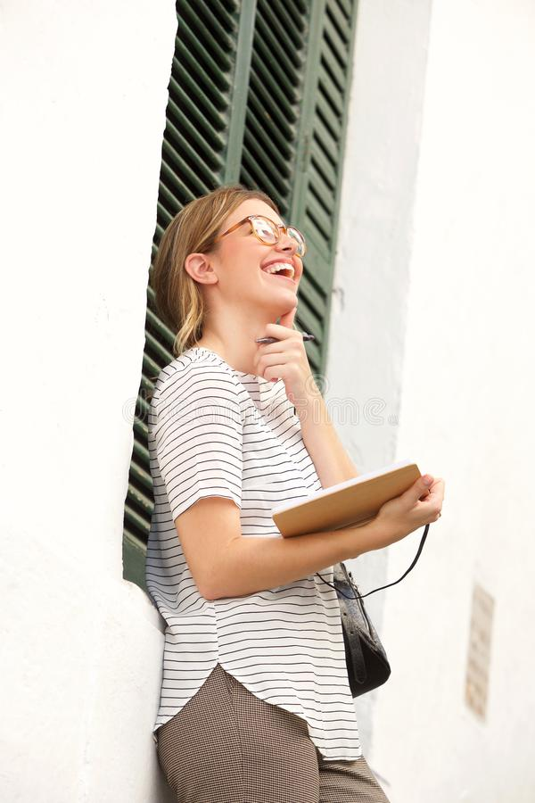 Jonge vrouw die en dagboek denken houden stock foto's