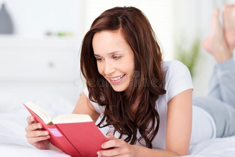 Jonge vrouw die en een boek ontspannen lezen royalty-vrije stock foto