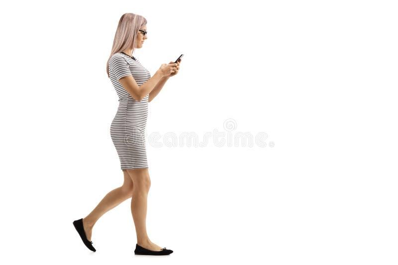 Jonge vrouw die en haar telefoon lopen bekijken royalty-vrije stock fotografie