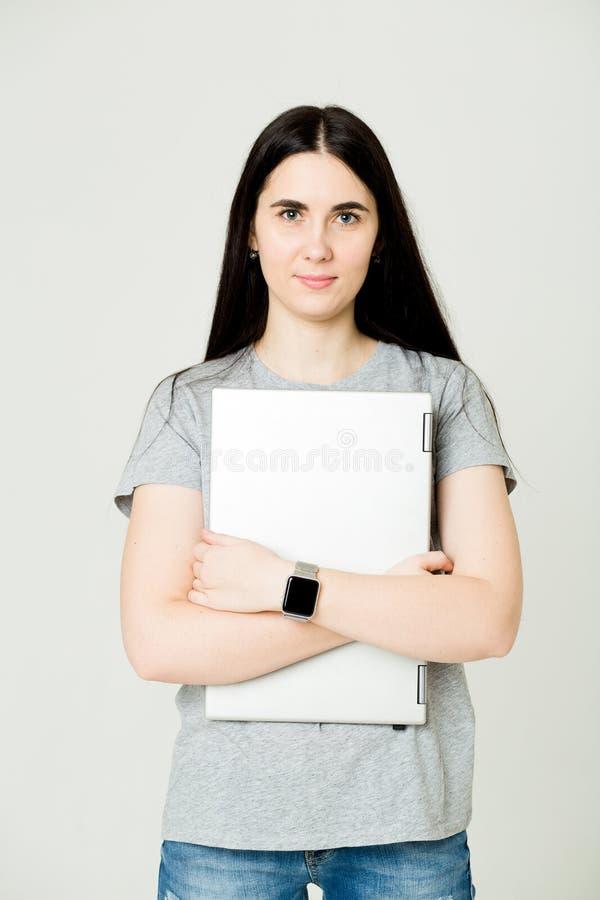 Jonge vrouw die en laptop bevinden zich houden Gelukkig jong meisje die haar die laptop met behulp van, op wit wordt ge?soleerd stock foto