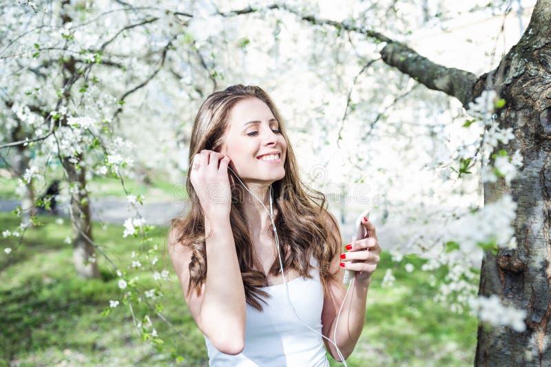 Jonge vrouw die en met gesloten ogen glimlachen die aan muziek op de telefoon met oortelefoons onder de bloeiende bomen luisteren royalty-vrije stock foto