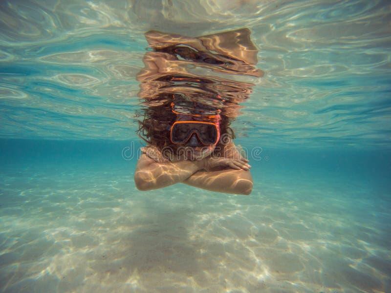 Jonge vrouw die en met masker en vinnen in duidelijk blauw water zwemmen snorkelen royalty-vrije stock foto's