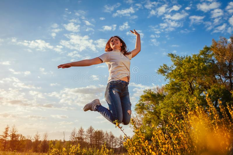 Jonge vrouw die en pret op de lentegebied springen hebben bij zonsondergang Het gelukkige en vrije meisje geniet van aard royalty-vrije stock foto