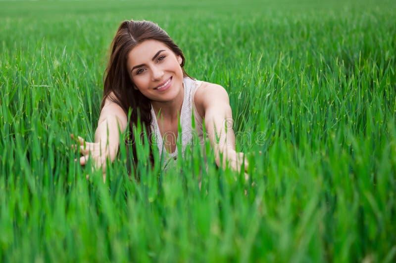 Jonge vrouw die en in vers groen FI ontspannen glimlachen royalty-vrije stock foto