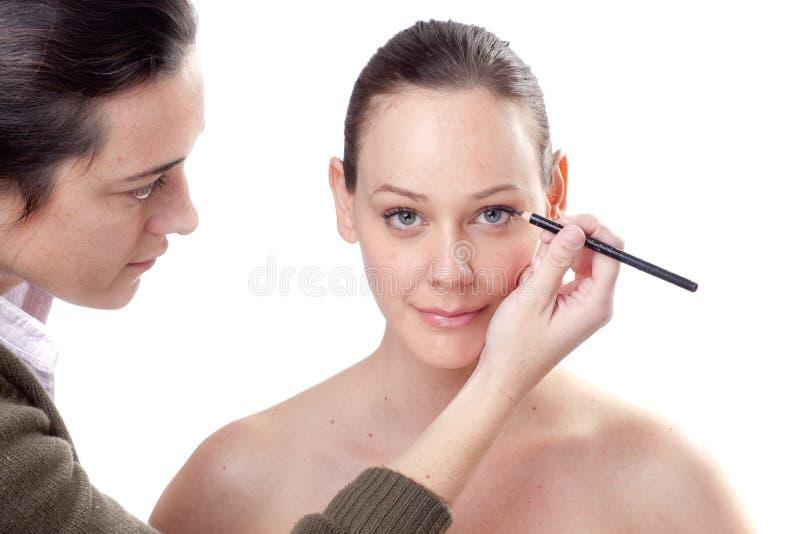Jonge vrouw die eyeliner toepast royalty-vrije stock foto
