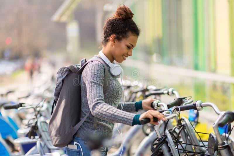 Jonge vrouw die fiets huren stock fotografie