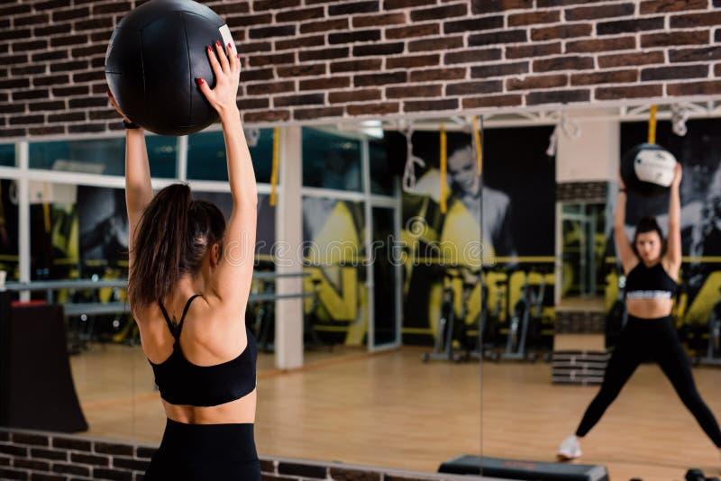 Jonge vrouw die fitballs in de gymnastiek voor een spiegel opheffen royalty-vrije stock afbeeldingen