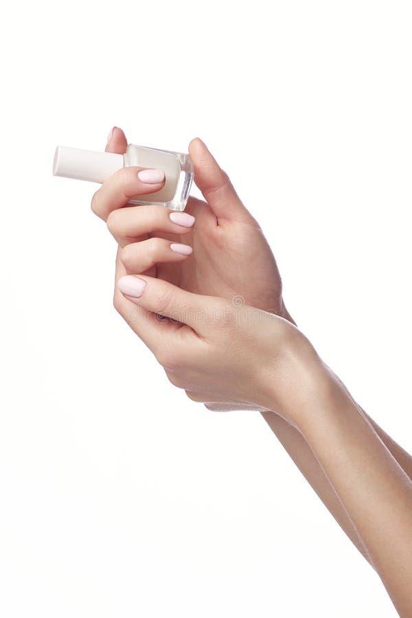 Jonge vrouw die fles acht nagellak tonen stock foto's