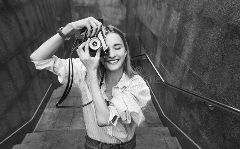 Jonge vrouw die foto, op een oude filmcamera nemen, dag, openlucht royalty-vrije stock foto's