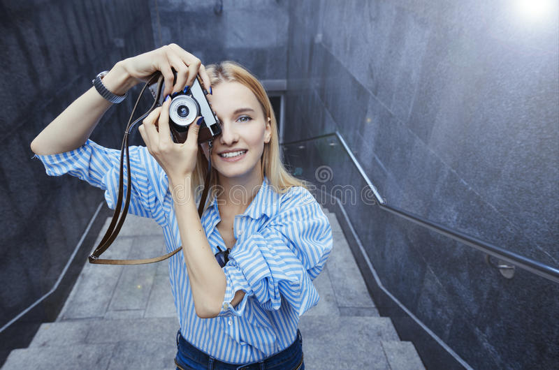 Jonge vrouw die foto, op een oude filmcamera nemen, dag, openlucht royalty-vrije stock afbeeldingen