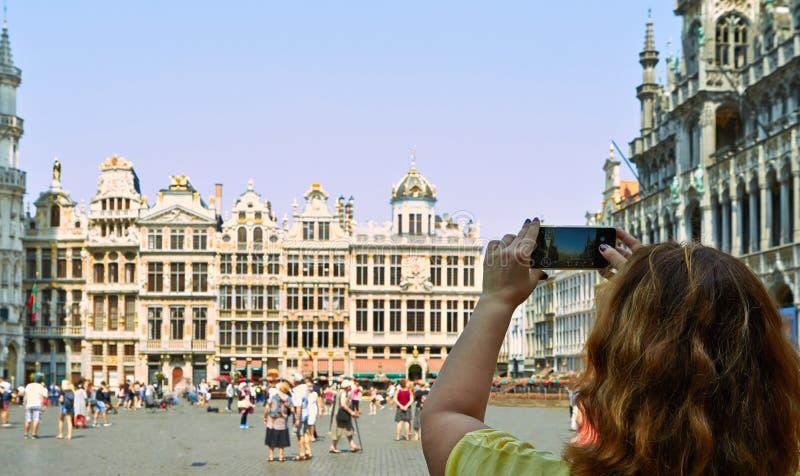 Jonge vrouw die foto van Grand Place in Brussel, België maakt stock fotografie