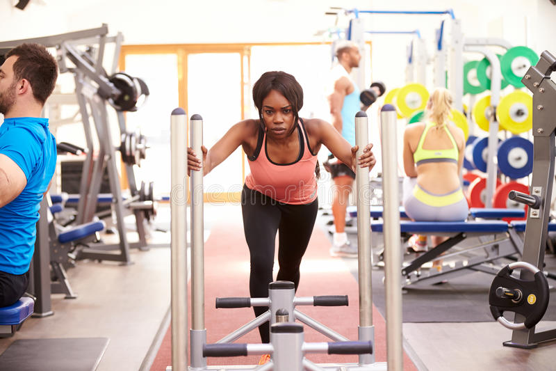 Jonge vrouw die gebruikend materiaal bij een gymnastiek uitwerken stock foto