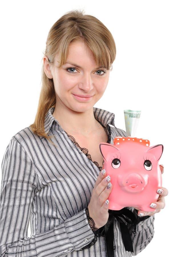 Jonge vrouw die geld in spaarvarken zet royalty-vrije stock fotografie