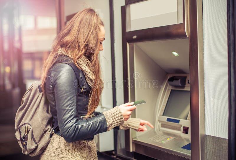 Jonge vrouw die geld van ATM nemen stock foto