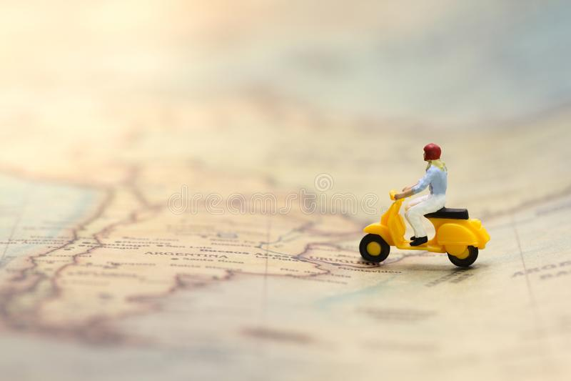 Jonge vrouw die gele cijferautoped berijden op uitstekende wereldkaart royalty-vrije stock afbeeldingen