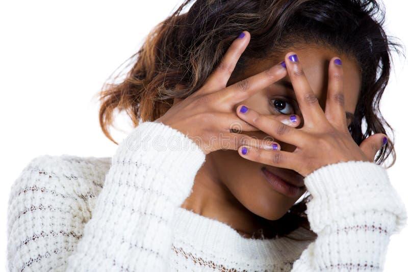 Jonge vrouw die gelukkig door haar vingers kijken stock fotografie