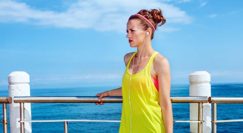Jonge vrouw die in geschiktheidsuitrusting opzij dijk bekijken royalty-vrije stock foto's