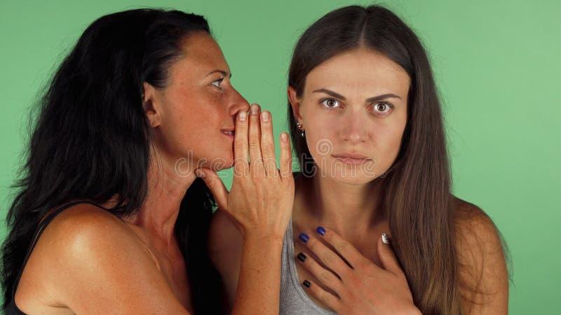 Jonge vrouw die geschokt terwijl haar vrienden die aan haar fluisteren kijken royalty-vrije stock afbeeldingen