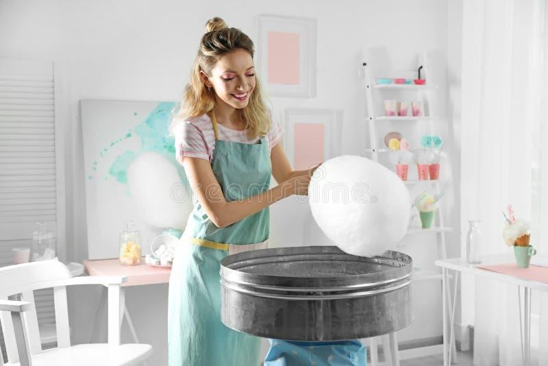 Jonge vrouw die gesponnen suiker maken die moderne machine met behulp van stock afbeelding