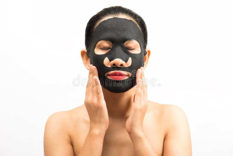 Jonge vrouw die gezichts zwart maskerblad met het zuiveren van masker doen royalty-vrije stock foto's