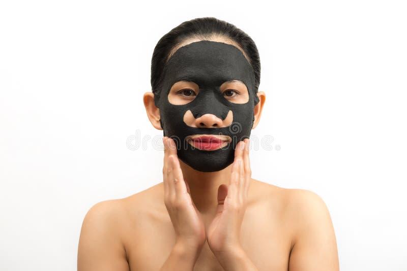Jonge vrouw die gezichts zwart maskerblad met het zuiveren van masker doen stock fotografie