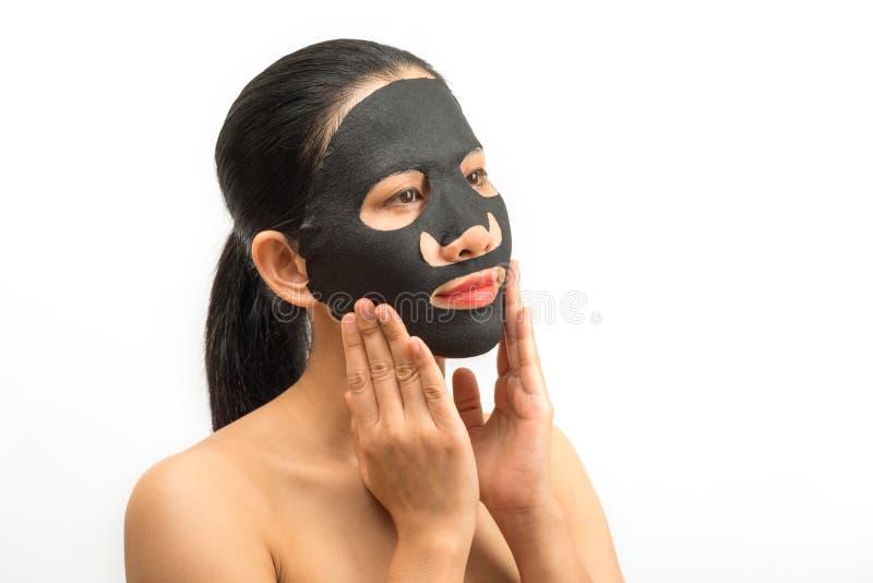 Jonge vrouw die gezichts zwart maskerblad met het zuiveren van masker doen royalty-vrije stock foto