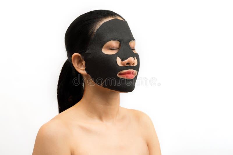 Jonge vrouw die gezichts zwart maskerblad met het zuiveren van masker doen royalty-vrije stock fotografie