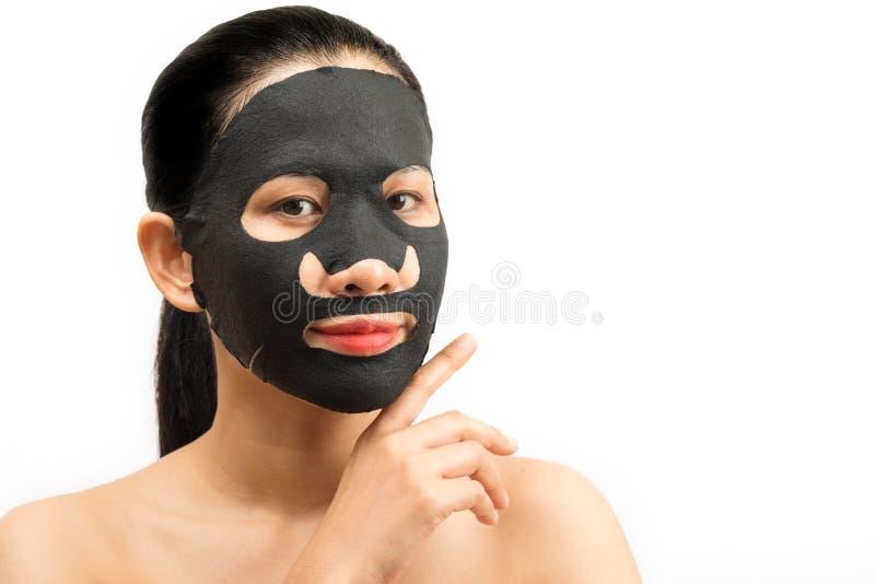 Jonge vrouw die gezichts zwart maskerblad met het zuiveren van masker doen stock foto's