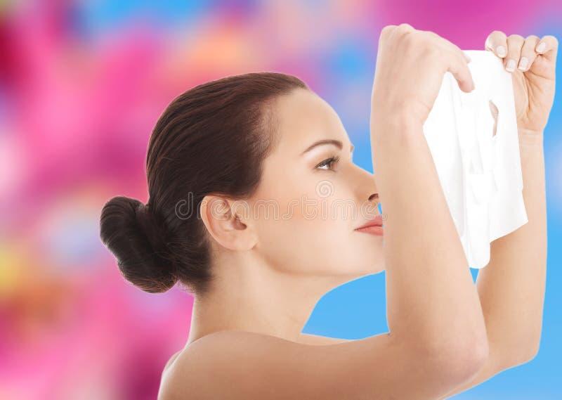 Jonge vrouw die gezichtsmasker krijgt royalty-vrije stock fotografie