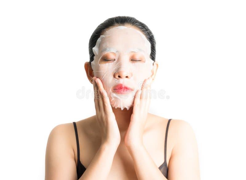 Jonge vrouw die gezichtsmaskerblad doen stock foto