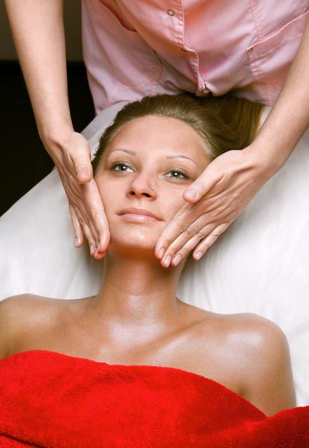 Jonge vrouw die gezichtsmassage in de schoonheidskliniek ontvangen stock afbeelding