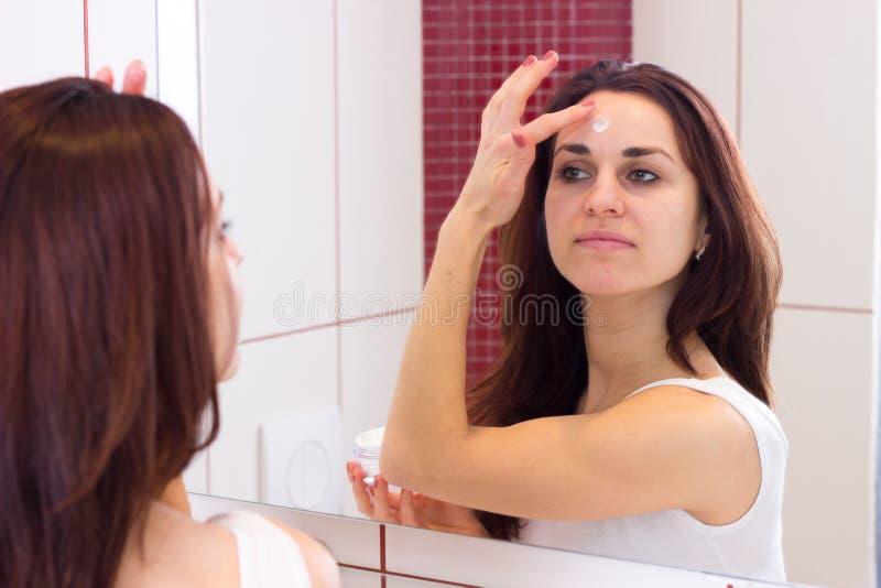 Jonge vrouw die gezichtsroom in badkamers gebruiken royalty-vrije stock foto's