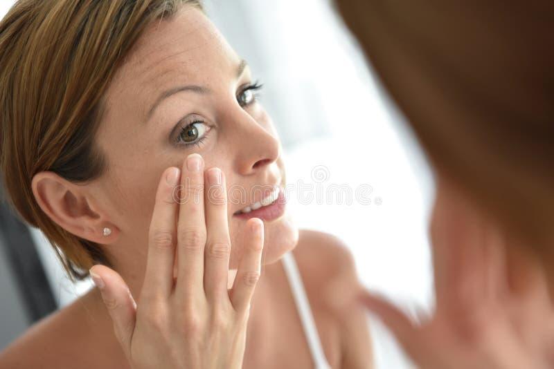 Jonge vrouw die gezichtsroom toepast stock afbeeldingen