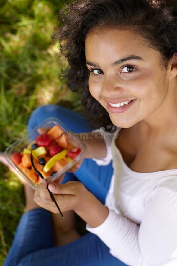 Jonge Vrouw die Gezond Vers Fruit in openlucht eten stock foto