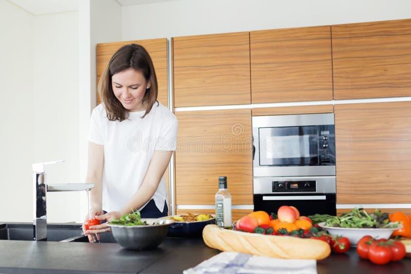 Jonge vrouw die gezond voedsel in de keuken koken royalty-vrije stock afbeeldingen