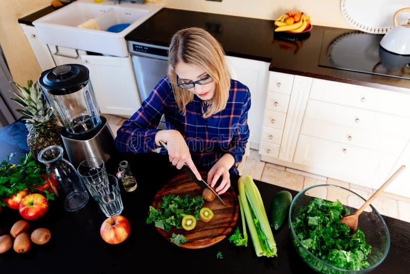 Jonge vrouw die gezonde maaltijd in keuken voorbereidt stock afbeeldingen
