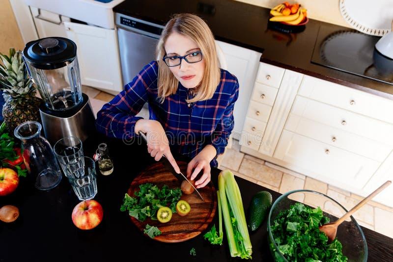 Jonge vrouw die gezonde maaltijd in keuken voorbereidt royalty-vrije stock afbeeldingen