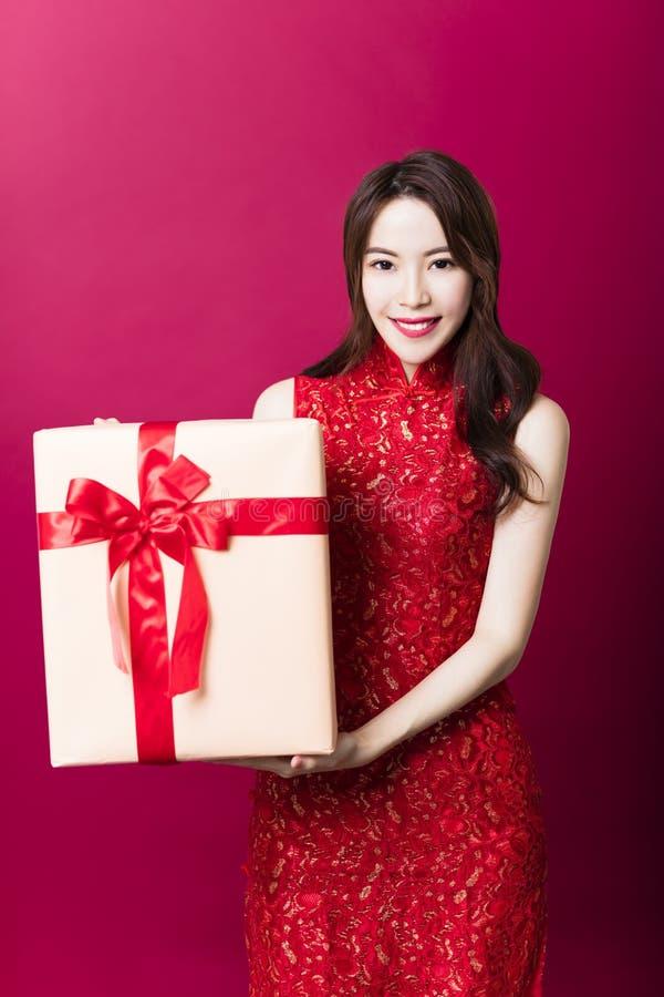 jonge vrouw die giftdoos voor Chinees nieuw jaar tonen stock fotografie