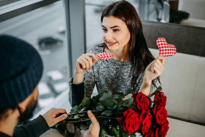 Jonge vrouw die giften met haar vriend ruilen bij restaurant V royalty-vrije stock afbeelding