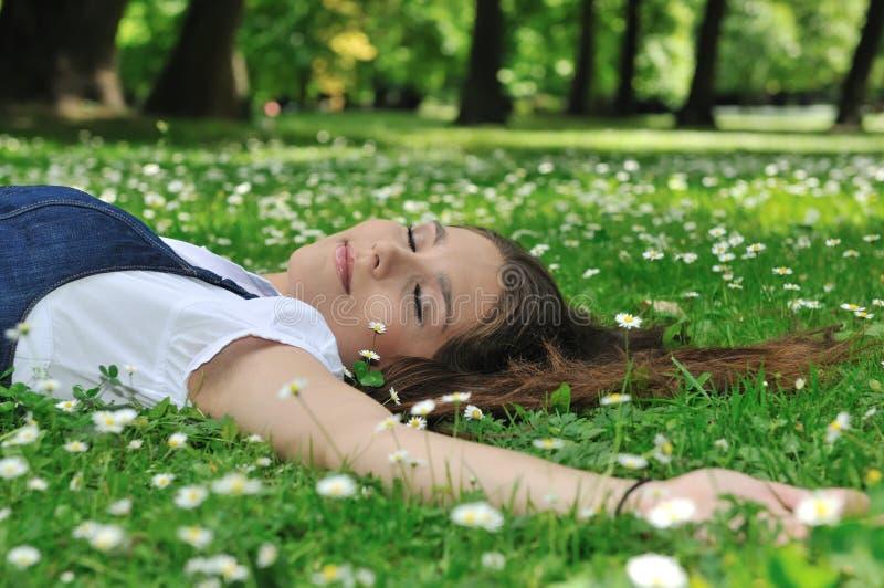 Jonge vrouw die in gras met bloemen ligt stock fotografie