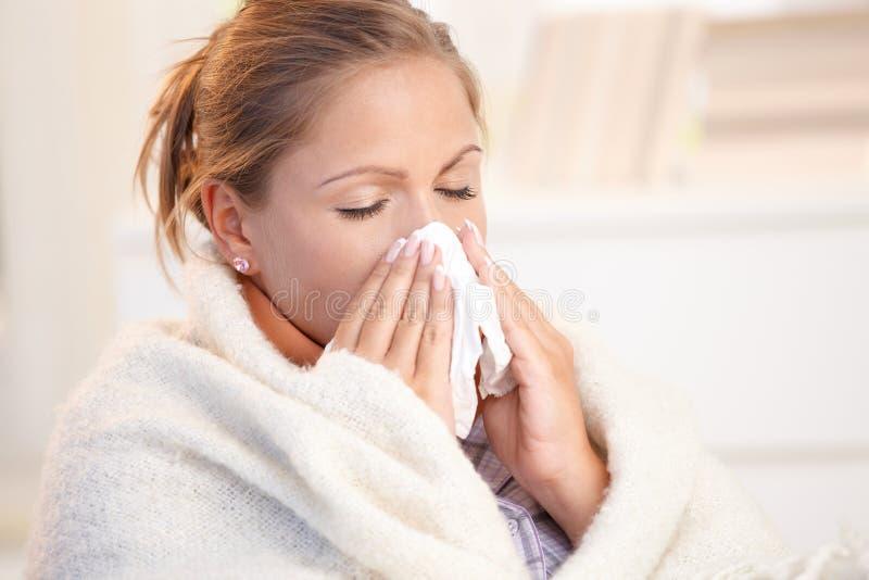 Jonge vrouw die griep heeft die haar neus blaast royalty-vrije stock foto