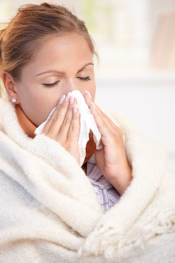 Jonge vrouw die griep heeft die haar neus blaast royalty-vrije stock fotografie